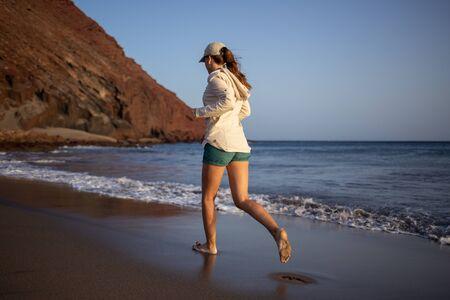 Young woman running on La Tejita beach, Tenerife , Spain. Slim girl having fun at the ocean beach of Tenerife Stock Photo