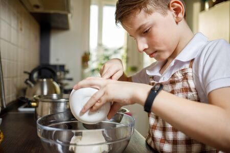 Small cute boy cooking dessert on the kitchen.