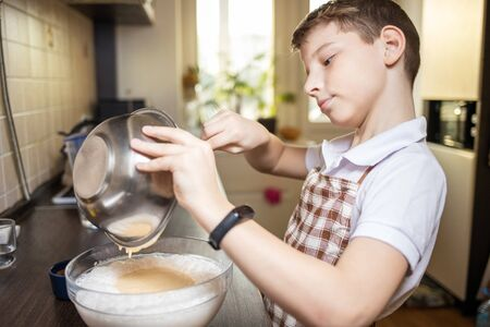 Small cute boy cooking dessert on the kitchen. Family cooking background. 版權商用圖片