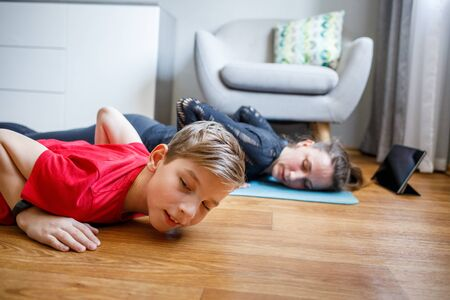 Small boy together with his mother practicing yoga at home during quarantine