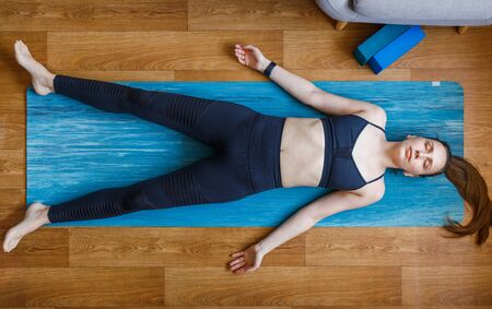 Young woman relaxing in shavasana pose. Practising pilates and yoga at home