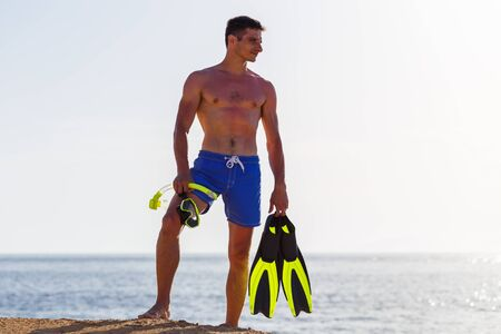 Young man with snorkelling equipment standing near the sea. Snorkelling on the vacations