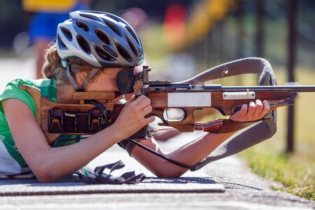 Young girl aiming her rifle on biathlon shooting range. Summer biathlon competition image with unrecognizable athlete