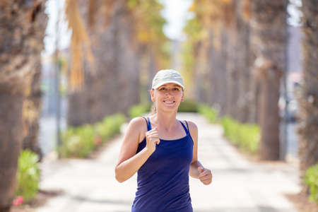 Portrait of young woman running on the palm alley on summer day. Fitness girl jogging on the street Stock Photo