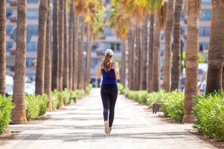 Back view of jogging woman on the street of tropical town. Running girl on summer day