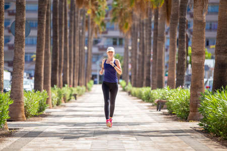 Smiling girl running on the street in tropical city. Slim woman jogging on the palm alley
