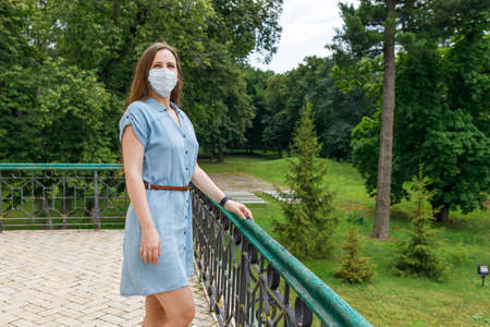 Young woman in medical mask visiting park as tourist during coronavirus pandemic Фото со стока