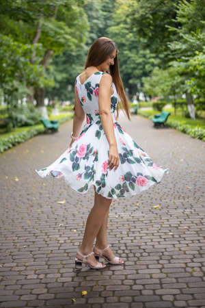 Happy young woman in new white dress dancing in park