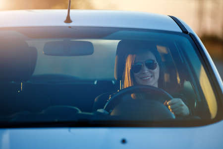 Young woman enjoying driving car at sunset. Travelling by automobile