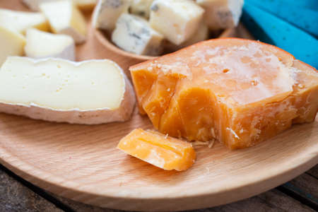 Close up image of different kinds of cheese on board. Cheese set