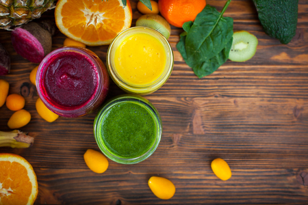 Blended green,yellow and purple smoothie with ingredients selective focus