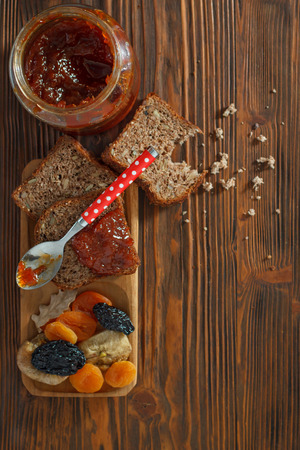 dry fruit: Wholemeal bread with apricot jam surrounded by dry fruit. VintageRetro style. Stock Photo