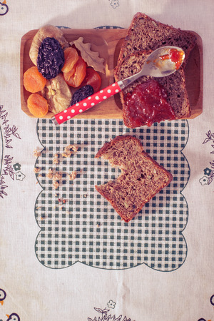 Wholemeal bread with apricot jam surrounded by dry fruit. VintageRetro style. photo