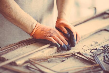 industry worker wearing used protection gloves making metal framework