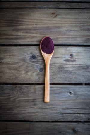 古い木製のテーブルのスプーンに赤い粉 (アロニア)