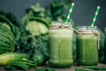 Blended groene smoothie met ingrediënten op houten tafel