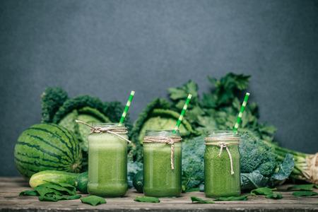 smoothies: Batido verde mezclado con los ingredientes en la mesa de madera Foto de archivo