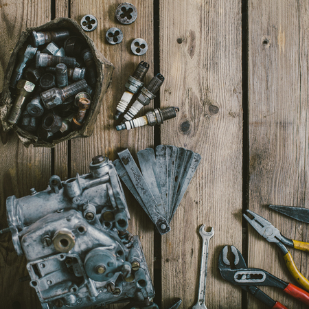 Carburetors for a car engine with tools on wooden table Stock Photo