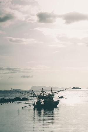 コ・パンガンの夕日シーンを持つ漁師ボート。垂直方向のイメージ。 写真素材