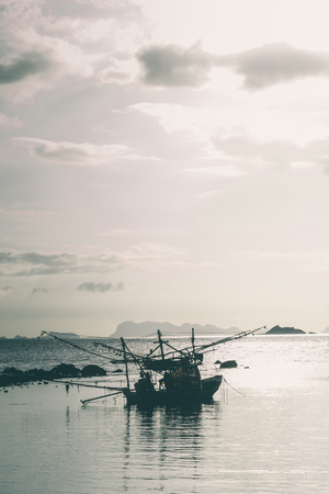 Fisherman boat with sunset scene in koh phangan. Vertical image.