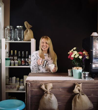 adds: Laughing girl adds milk to the cup with coffee in cafe. Young woman barista working in coffee shop Stock Photo