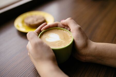 Cup of coffee latte with a heart symbol. Womans hands holding cup of coffee latte in a cafe. Soft focus Stock Photo