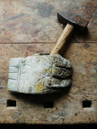 workbench: Glove holding hammer on old work-bench.