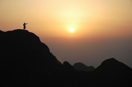 top of mountain: Man on top of the mountain during sunset.