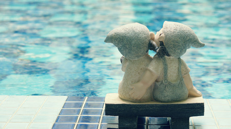 A girl and a boy dolls, kissing each other, sitting near the pool  love concept   photo