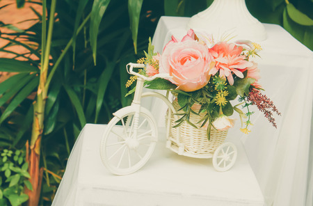 Mixed artificial flowers in small white bicycle vase and basket mixed artificial flowers in small white bicycle vase and basket on white table in garden mightylinksfo