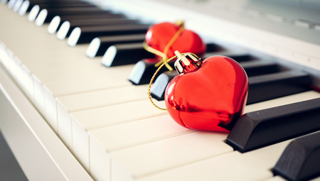 Two red glossy hearts on piano keyboard, love and vintage concept