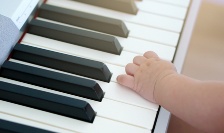 Babys little hand on piano keyboard
