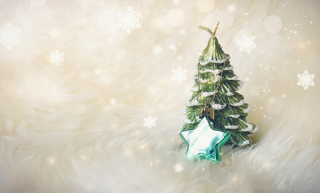 small christmas tree with a green star on white fur surrounded with glitter star dust - White Mini Christmas Tree