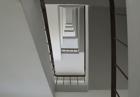 stairwell: looking up stairwell building. Abstract architecture background.