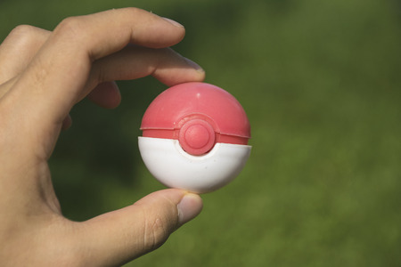 poke: Thailand - August 20, 2016: Poke ball in Hand  (Pokemon Ball). Pokeball toy of the game Pokemon Go at Chon Buri, Thailand.