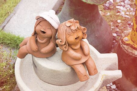 earthenware: Earthenware or ceramics kid doll smilelaugh and sitting in garden. happy moment action.
