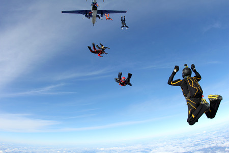 man flying: The group of skydivers are jumping out of a plane. Stock Photo