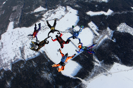 man flying: Skydivers are in the winter sky.