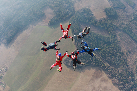 man flying: Six skydivers have made a circle figure.
