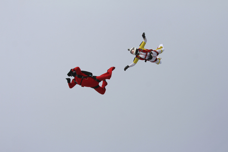 man flying: White woman skydiver and red man skydiver Stock Photo