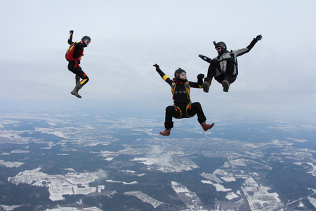 Three skydivers are having fun in the sky