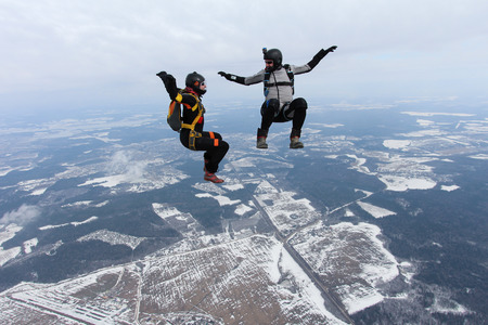 man flying: Two skydivers are sitting together in the sky.