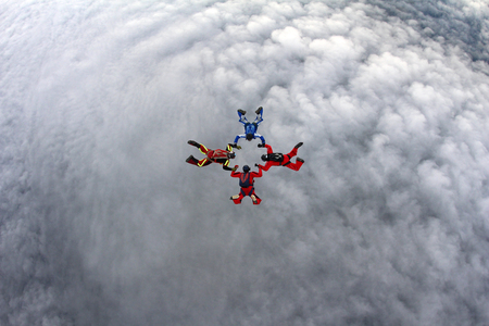 Four skydivers are above the white clouds.