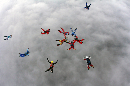 Skydivers are forming formation above the clouds. Stock Photo - 78228375
