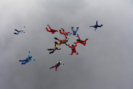 man flying: Skydivers are making a figure in the sky Stock Photo