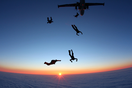 man flying: Sunset skydiving exit