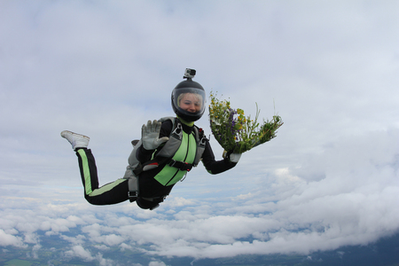 Skydiving girl with flowers is flying in the sky.