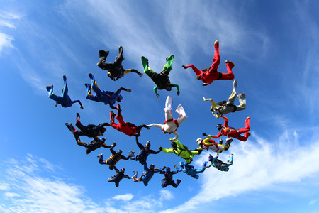 Skydivers are making a formation in the sky.