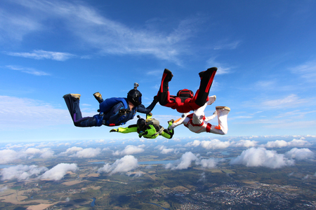 Four skydiver are training in the sky. Imagens