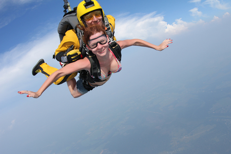 Skydiving. Girl and tandem-master are flying in the sky. 版權商用圖片 - 95562079